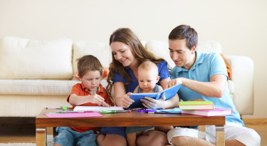 Young happy family with two kids drawing and reading together